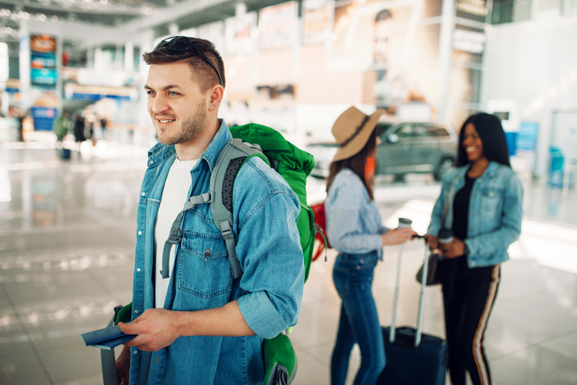 Male tourist with backpack holds passport in airport
